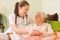 The caregiver helps the old woman to sleep